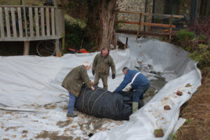 Garden pond liners being installed into a complex shaped pond